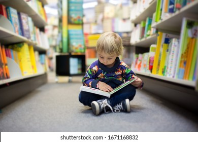 Adorable little boy, sitting in a book store and read book