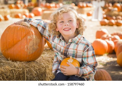 Adorable Little Boy Sitting and Holding His Pumpkin in a Rustic Ranch Setting at the Pumpkin Patch.