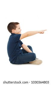 Adorable little boy sitting on floor pointing empty copy space. Isolated on white background