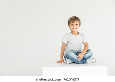 adorable little boy sitting and smiling at camera isolated on white