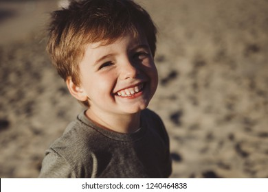 Adorable little boy smiling and being cheerful at the camera