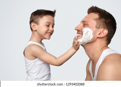 Adorable little boy in tank top cheerfully smiling and smearing shaving foam on face of happy man on white background