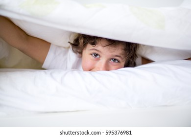 An Adorable little boy in white t-shit lying in bed