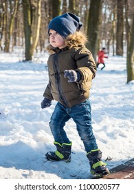 Adorable little boy in winter clothes at winter park background