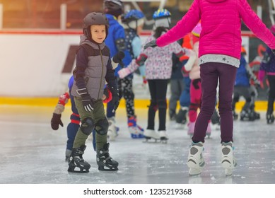 Adorable little boy in winter clothes with protections skating on ice rink