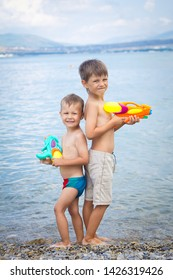 Adorable little boys playing with water guns on hot summer day. Cute children having fun with water outdoors. Funny summer games for kids.