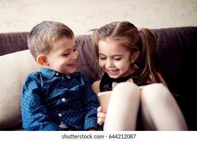 Adorable little brother and sister, having fun wit tablet computer. Playing games and laughing.