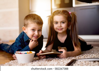 Adorable little brother and sister playing video games, smiling and looking happy, enjoying nice day