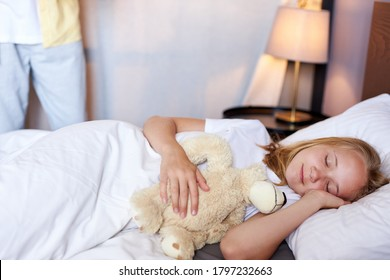 adorable little caucasian girl sleep on bed, hugging toy. sweet dreams, bedtime. in the morning. someone in the background going to wake her up