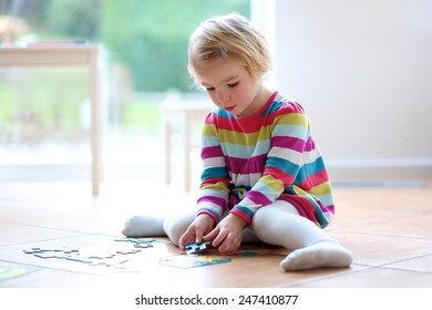 Adorable little child, blonde toddler girl, playing with puzzles sitting on the tiles floor next to a big window at home or kindergarten