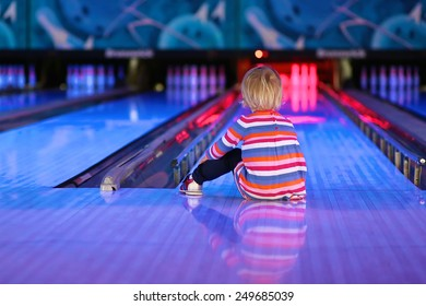Adorable little child, blonde toddler girl, sitting on the floor at bowling club waiting for a strike - weekend family leisure concept