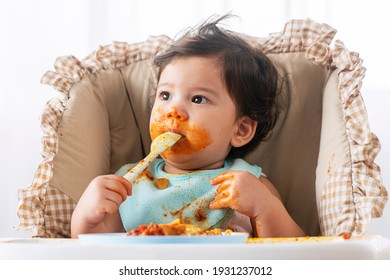 Adorable little child funny girl eating spaghetti with spoon while sitting in high-powered chair at home. Toddler child with tomato sauce making mess her face looking at parent. Self-feeding concept