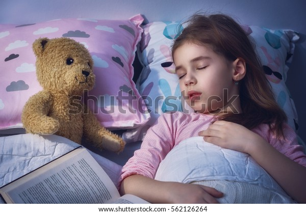 Adorable little child girl is napping in the bed. Quiet sleep with teddy bear after reading book.