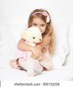 Adorable little child girl sit in the bed with her toy. The child girl hugs the teddy bear.