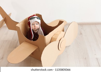 Adorable little child playing with cardboard plane indoors