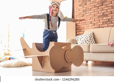 Adorable little child playing with cardboard plane at home