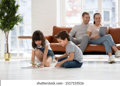Adorable little children brother and sister sitting on heated warm wooden floor in living room, drawing or painting pictures with multicolored pencils, while happy parents using tablet on couch.