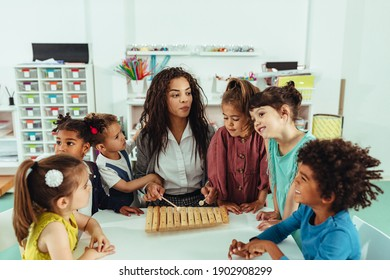 Adorable little children and their teacher playing at kindergarten