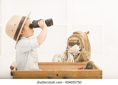 Adorable little explorer girl in a safari hat and explorer clothes with binoculars playing Safari sitting in a old wooden suitcase. Little child playing treasure hunt. Looking for the summer vacation