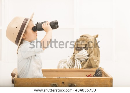 0e446a59f0b0e Adorable little explorer girl in a safari hat and explorer clothes with  binoculars playing Safari sitting