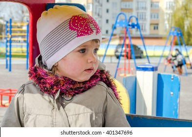 Adorable little girl baby with beautiful eyes, playing on a wooden swing at the amusement park, dressed in a raincoat with a hood, a hat with a bow and a scarf enjoying happy emotions