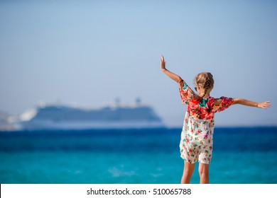 Adorable little girl at beach background big lainer in Greece