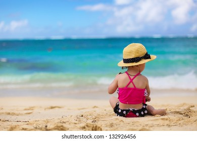 Adorable little girl in beautiful swimsuit at tropical beach