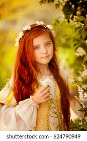 Adorable little girl in blooming apple tree