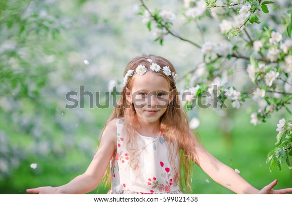 Adorable little girl in blooming apple tree garden on spring day