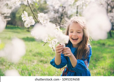 Adorable little girl in blooming cherry tree garden on beautiful spring day. Cute child picking fresh cherry tree flowers at spring.