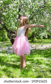 Adorable little girl in blossoming apple orchard