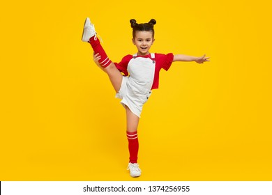 Adorable little girl in bright outfit lifting leg and smiling while dancing against yellow background. Dancing class for kids concept