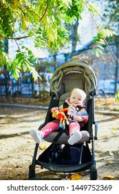 Adorable little girl in bright stylish clothes sitting in pushchair outdoors on a fall day. Autumn walks with kids