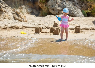 Adorable little girl building sand castles on beach during summer holiday vacation