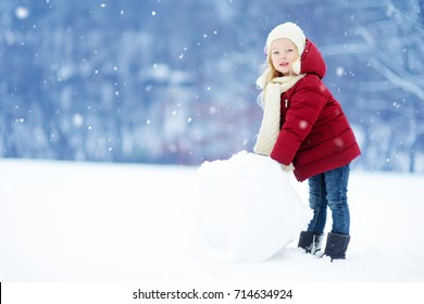 Adorable little girl building a snowman in beautiful winter park. Cute child playing in a snow. Winter activities for kids.