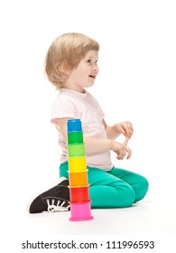 Adorable little girl building toy pyramid on white background