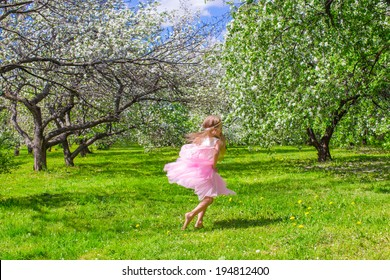Adorable little girl with butterfly wings have fun in blossoming apple orchard