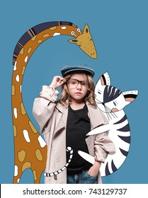 Adorable little girl in cap, overcoat and eyeglasses standing with magic drawn animals and looking at camera