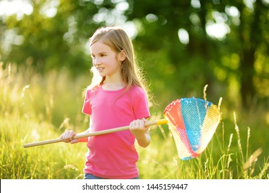 Adorable little girl catching butterflies and bugs with her scoop-net. Child exploring nature on sunny summer day. Family leisure with kids at summer.