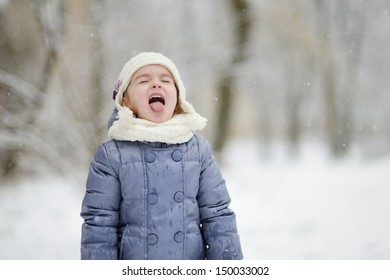 Adorable little girl catching snowflakes with her tongue
