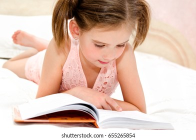 Adorable little girl child is reading a book on the bed