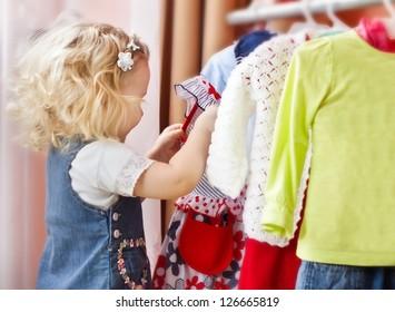 Adorable little girl choosing clothes