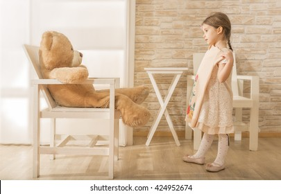 Adorable little girl choosing the perfect dress for herself. Beautiful little girl asking teddy bear to help her to choose the perfect outfit. Choose Clothes