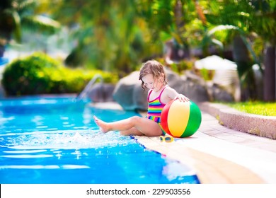Adorable little girl with curly hair wearing a colorful swimming suit playing with water splashes at beautiful pool in a tropical resort having fun during family summer vacation