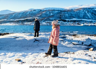 Adorable little girl and cute boy enjoying snowy winter day outdoors at beach surrounded by fjords in Northern Norway