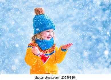Adorable little girl, cute toddler in a blue knitted hat and yellow sweater, playing with snow, catching snowflakes and ringing her Christmas toy bell, having fun outdoors in a beautiful winter park