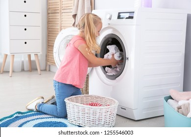 Adorable little girl doing laundry at home