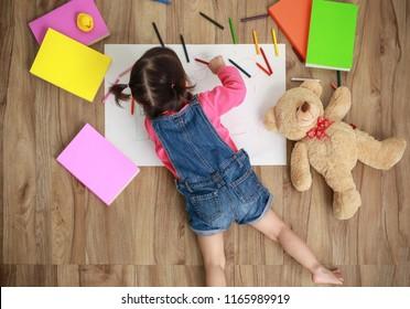 Adorable little girl drawing artwork. Studio shot top view of child on floor