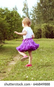 Adorable little girl dressed in a fluffy purple tutu skirt playing in a summer park in the countryside.