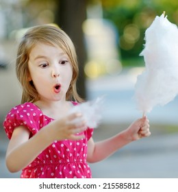 Adorable little girl eating candy-floss outdoors at summer